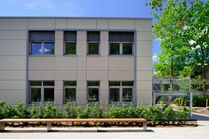 Die Architekten entschieden sich für eine Vorhangfassade aus zementgebundenen Faserplatten in unterschiedlichen mattierten Naturfarben. In Portalrahmen gefasste Fensterbänder betonen einzelne Bereiche und gliedern die Fläche