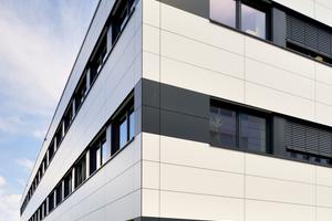Liegende Fensterbänder, eingerahmt in anthrazitgraue Fassadenelemente, und die schwarz hinterlegten Horizontalfugen im Fassadenbild unterstreichen die dynamische Form des Modulgebäudes