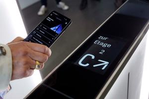 Mit dem Aufzug erreichen die Mieter die Lobby im Erdgeschoss. Dort passieren sie eine Sensorschleuse. Lesegeräte verbinden sich via Bluetooth mit dem Smartphone und zeigen den Aufzug an, der ohne Wartezeit und zusätzlichen Knopfdruck automatisch auf die gewünschte Etage fährt