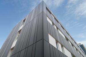 Die Planer entschieden sich für eine hinterlüftete Vorhangfassade aus glatten, unterschiedlich breiten Aluminiumkassetten in edlen, dunklen Anthrazit-Tönen