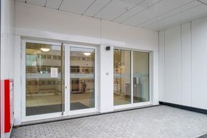 Der Haupteingang wurde in die Fassadenlängsseite eingeschnitten und mit weißen Fassadenpaneelen akzentuiert. Er bietet einen wettergeschützten Bereich und mündet in das Foyer mit Treppenhaus und Aufzugsanlage