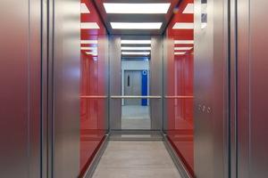 """Moderne Kabinengestaltung: perlgestrahltes Edelstahl und farbig hinterlegtes Glas entsprechen dem Unternehmensleitbild """"bunt"""""""