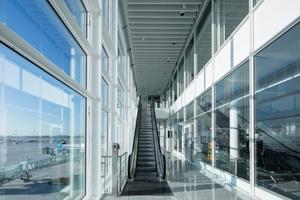 Blick in die Klimafassade: Hier befinden sich die Rolltreppen, mit denen die Fluggäste zwischen den drei Passagierebenen wechseln können. Der gesamte Umsteige- und Bewegungsverkehr der Passagiere wird über die Klimafassade auf einer Ebene geregelt, sodass man nur eingeschossige Fluggastbrücken benötigt<br /><br />